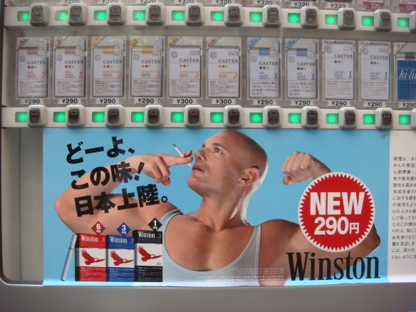 Taken at the end of my street in Tokyo. Dispensing machines for anything and everything are everywhere but the advertising on this one got me every time I walked past it.  Smoke and you'll turn into a muscled westerner?